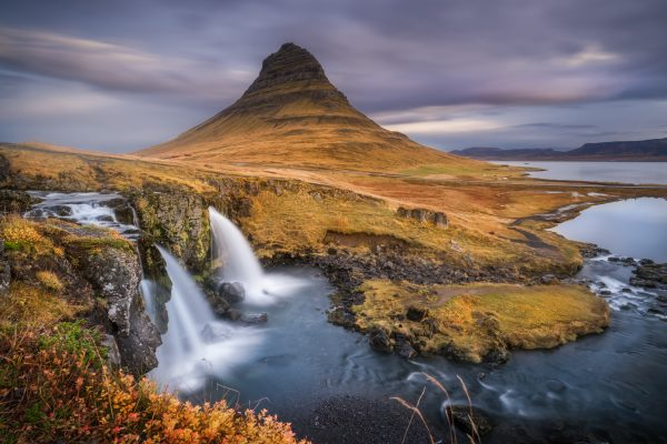 The beautiful Kirkjufell mountain and waterfall at sunrise during autumn.